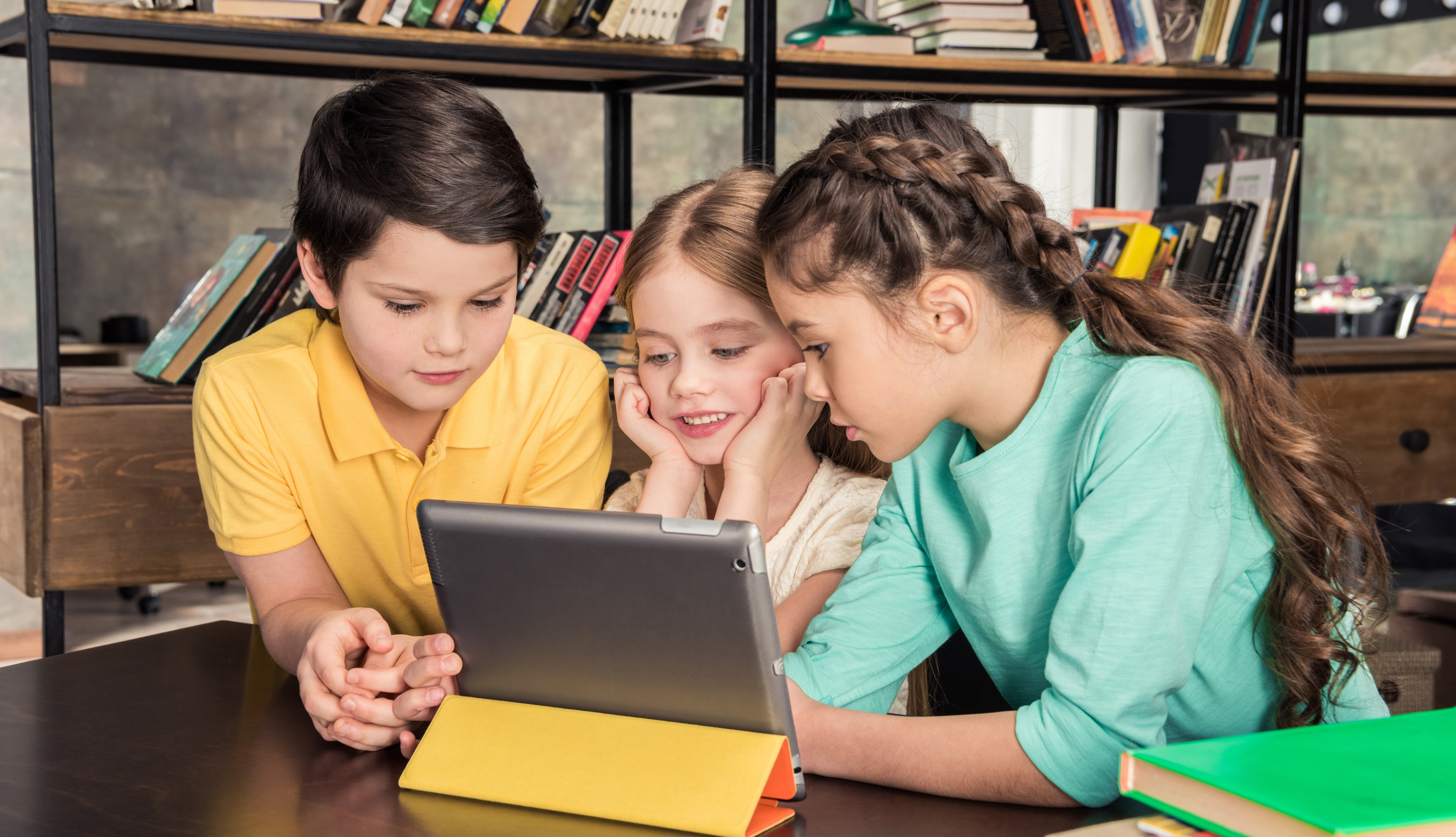 Concentrated schoolchildren using digital tablet in library