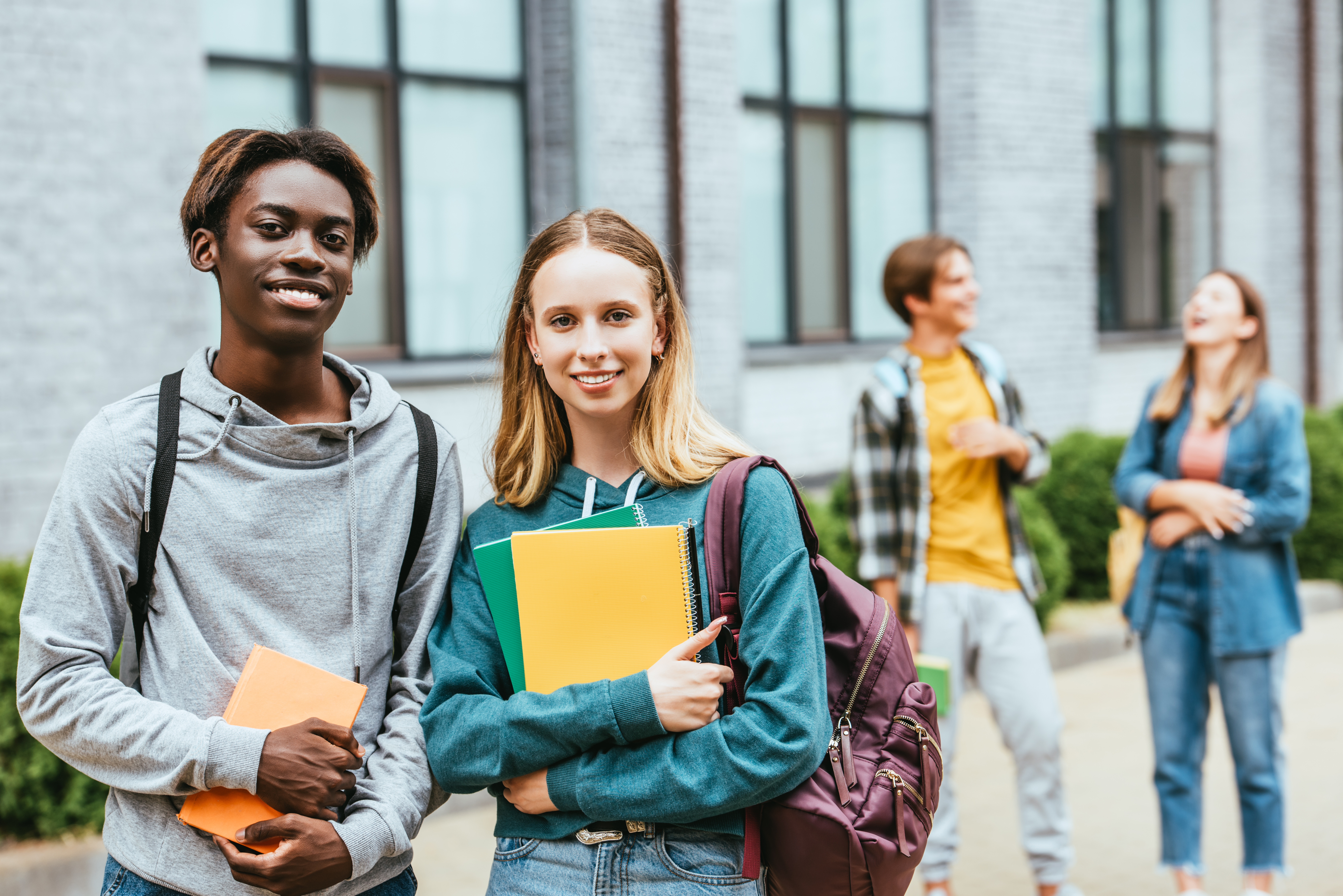 Selective focus of smiling multiethnic teenagers with backpacks and notebooks looking at camera outdoors
